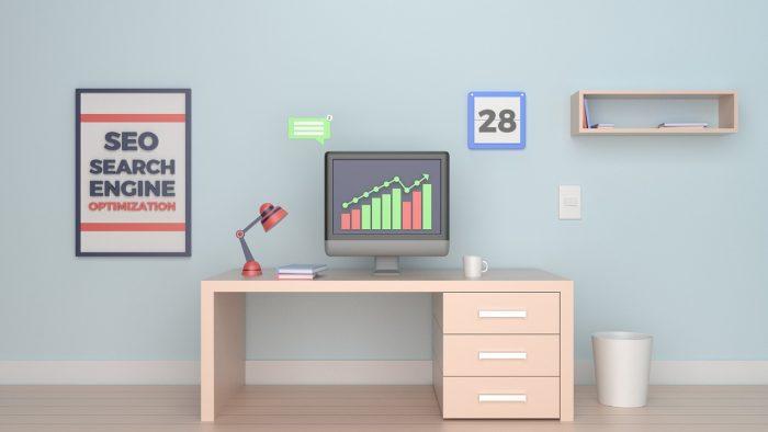 SEOという名前のポスター、机、机上のグラフが表示されているディスプレイ